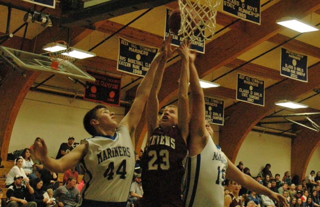Mariners Mason Oliver (left) and Ethan Shepard fight for the rebound with Eagle Max Mattson. Photo by Jack Scott