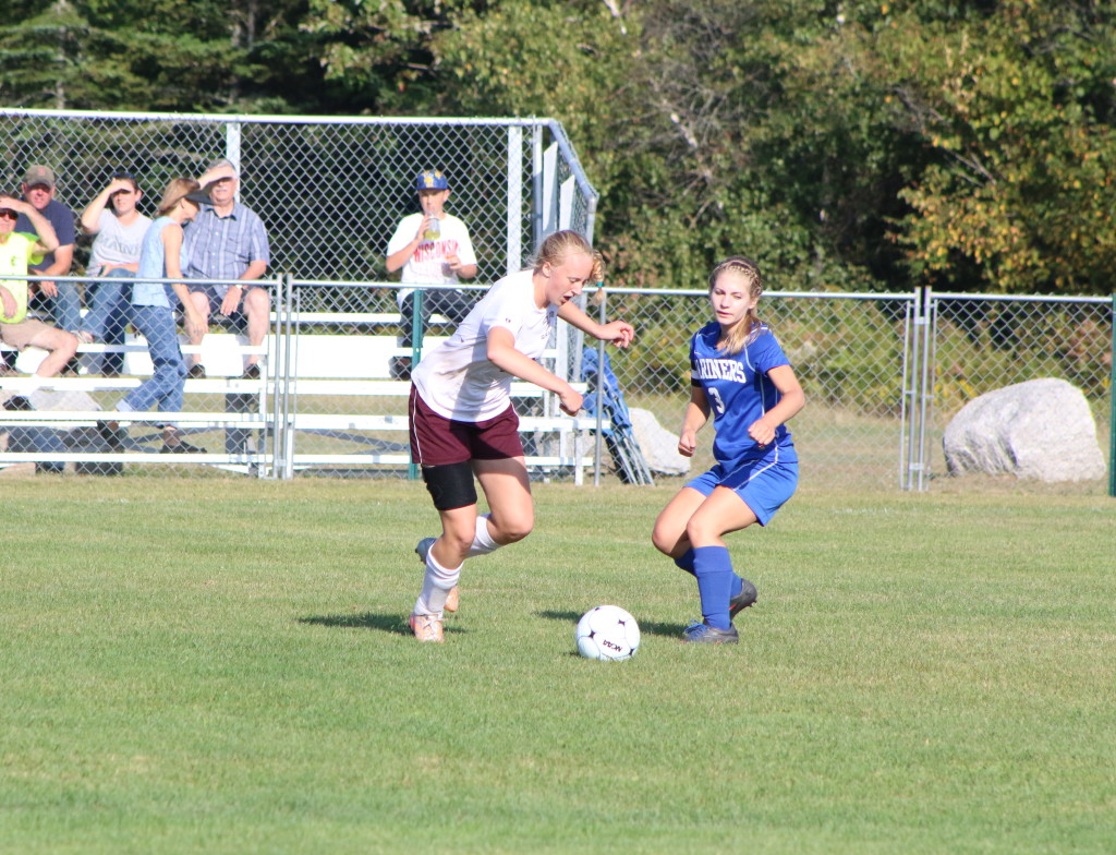 Eagle Alyssa Chesney and Mariner Ashley Haskell scramble to control the ball. Photo by Anne Berleant