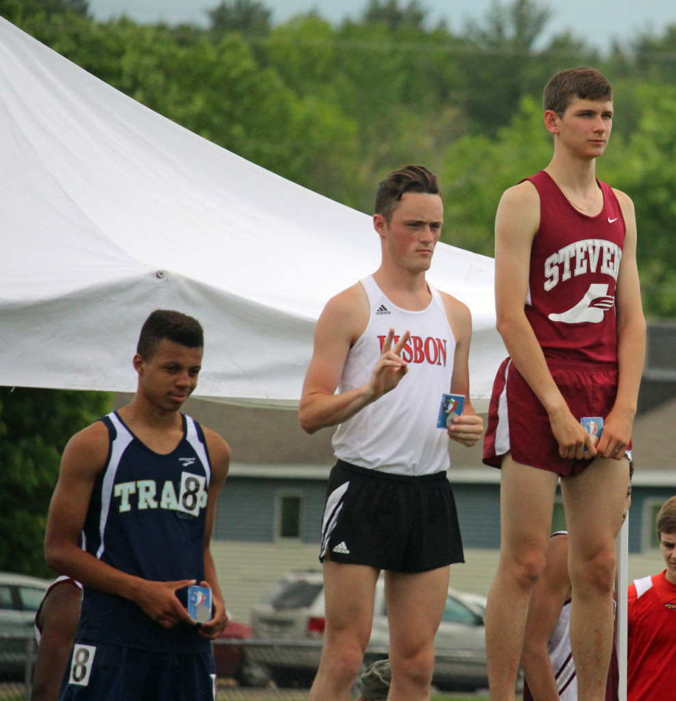 John Hassett, state champion in the 1600 meter run, on the winners podium. Photo by John Richardson