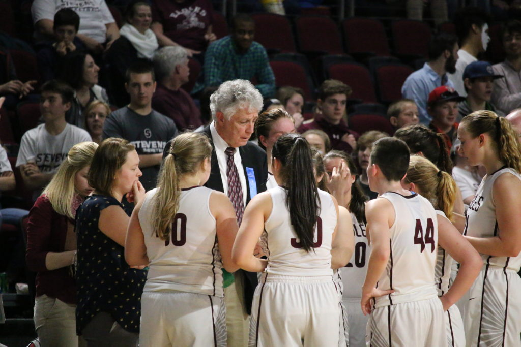 Coach Bill Case counsels his team. Photo by Anne Berleant