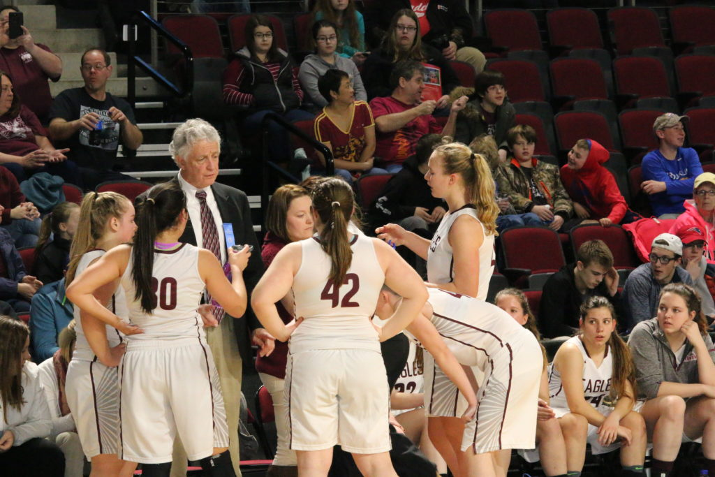 Head coach Bill Case talks through the next play with his team during a timeout. Photo by Monique Labbe