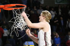 Beckett Slayton takes down the net after the win. Photo by Anne Berleant